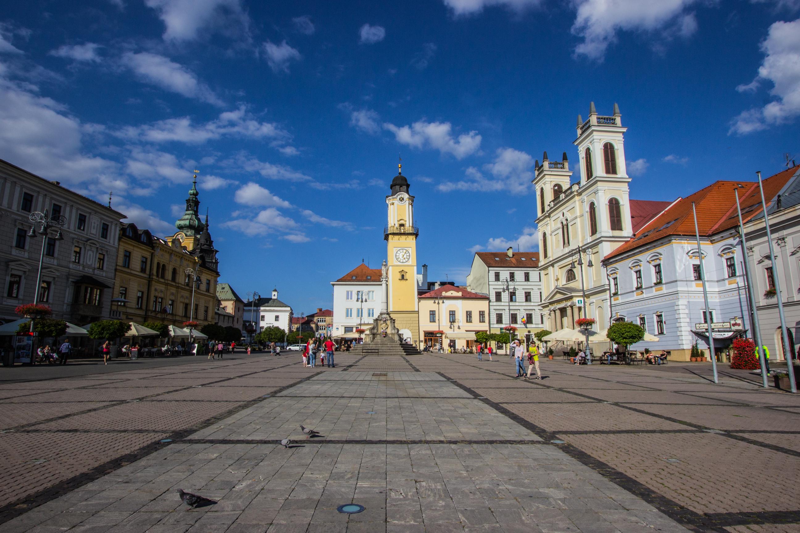 Górna część Placu Słowackiego Powstania Narodowego. W centrum wieża zegarowa, po prawej Katedra św. Franciszka Ksawerego w Bańskiej Bystrzycy.