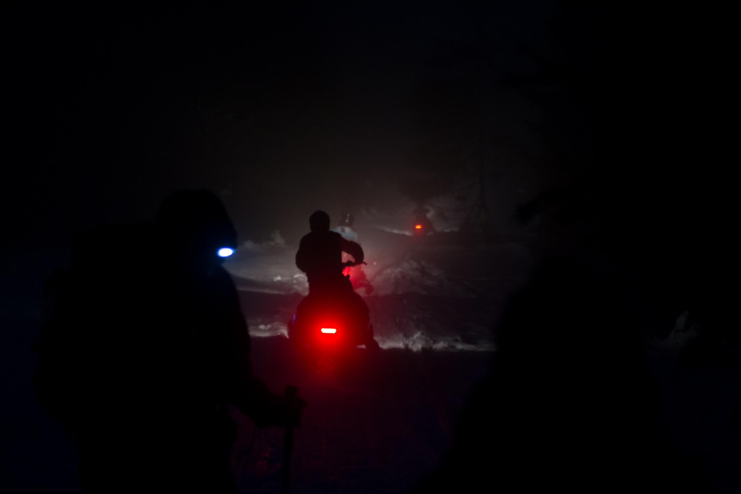 Oddalające się nocą skutery śnieżne