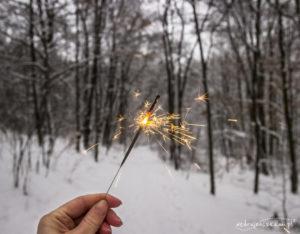 Dłoń trzymająca zimne ognie w ośnieżonym lesie